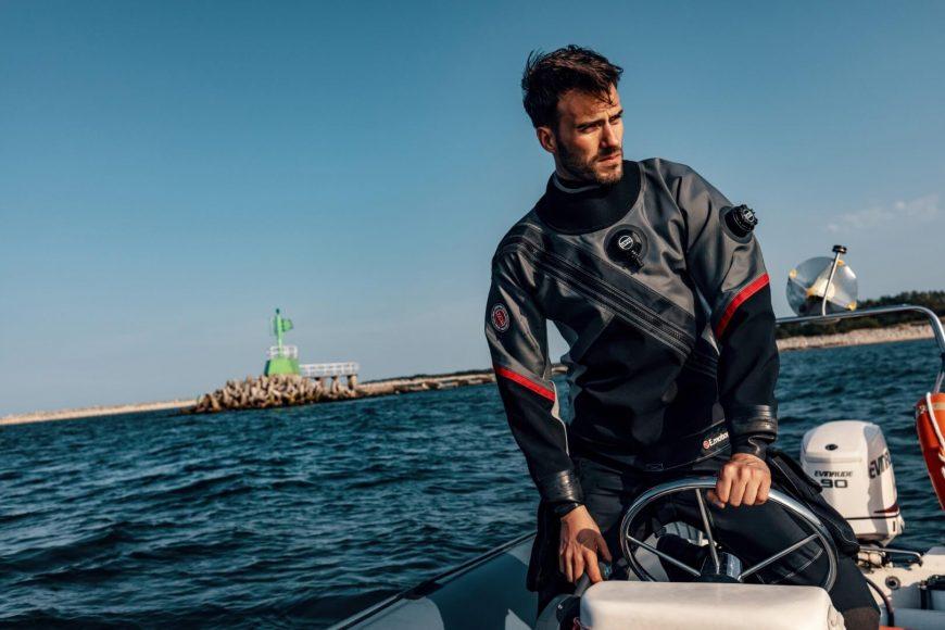 Taucher in grau/rot/schwarzem Santi-Trockentauchanzug der ein Boot steuert