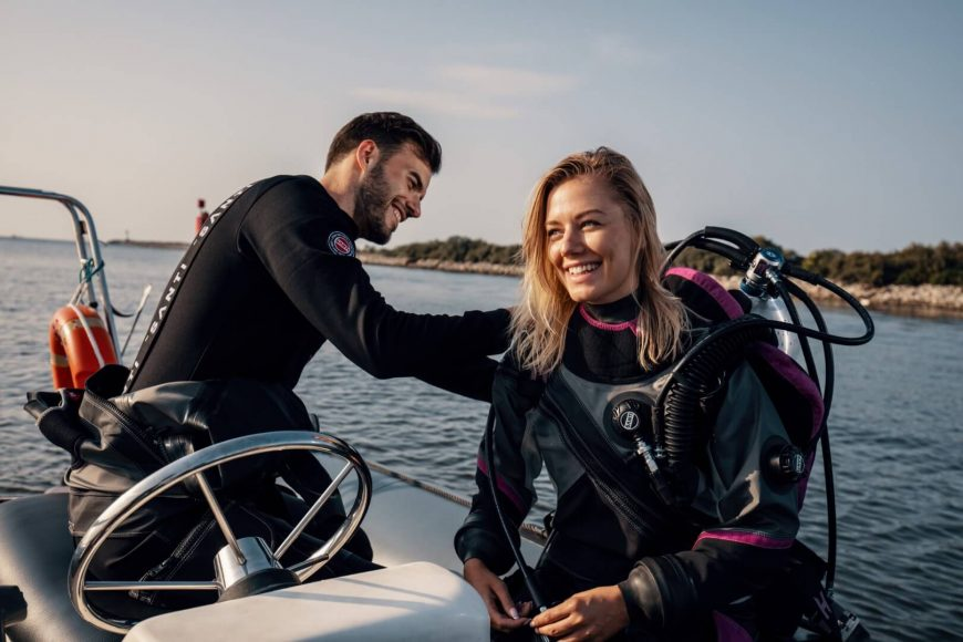 Zwei Taucher auf einem Boot mit schwarz und schwarz/pinken Santi-Trockentauchanzügen